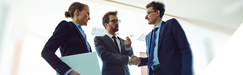 Two businessmen confirming a deal with a handshake, an assistant is standing beside them